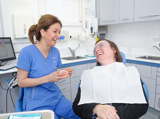 maryam jahangiri giving a patient a check up at penerley road dental surgery