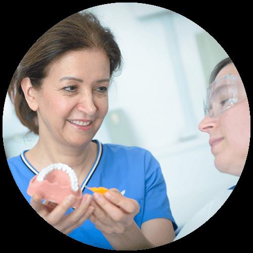 maryam jahangiri giving a patient a demonstration using a teeth mould at penerley road dental surgery